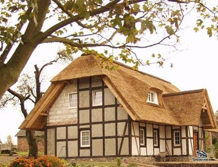 Dom z muru pruskiego z szarym wypełnieniem kryty strzechą