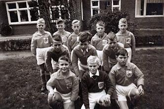 Photo: Oranjevereniging optocht koninginnedag Het voetbalelftal 30 april 1959. v.l.n.r. staand Jan Kleef, Gerrie Bruining, Jan Enting, Hans Homan en Bé Hadderingh middelste rij: Bram Hadderingh, Jan Moek en Geert Niemeijer Wzn. voor: Rikus Harms, Wim Lammerts en Evert Mennega. Ze hadden een witte gymnastiekbroek aan en een blouse van oranje papier en Egbert Bruining had er een leeuw op gemaakt. Ze hadden blauw papier om hun benen voor kousen. Wim Lammerts was keeper, die had een grijze trui met een witte broek aan. Op het sportveld waren spelletjes, zoals met een ei op een lepel lopen, zak lopen of op een fiets om wat melkflessen rijden of je moest wasgoed ophangen.
