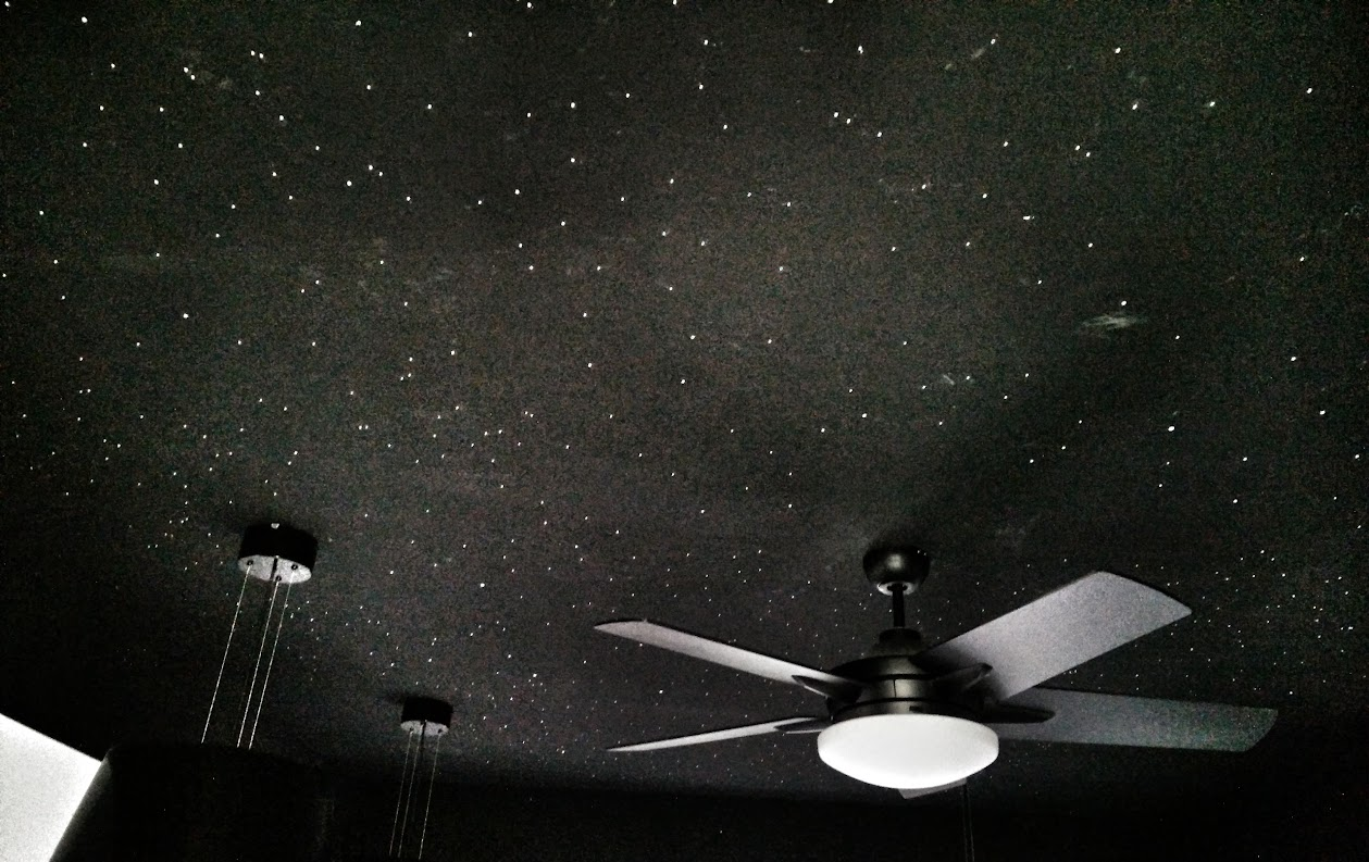 A black bedroom ceiling covered with small white glow-stars