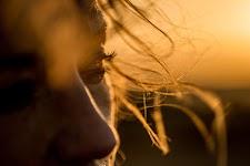 haren naast gezicht van een meisje in oranje gloed