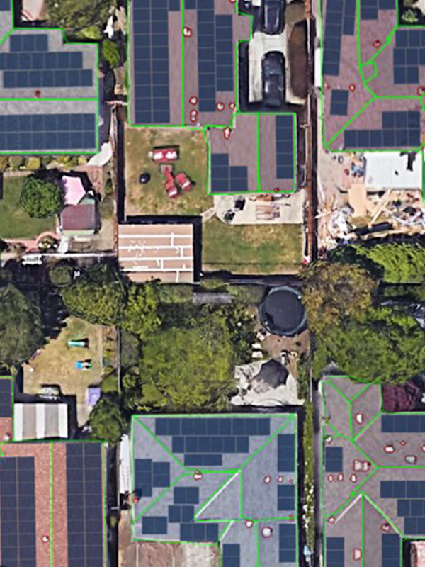 An aerial photo showing homes with solar panels. Lines are overlayed to divide each roof into regions based on their angle