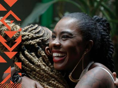 Duas mulheres negras se abraçam
