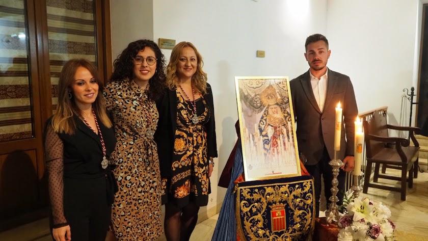 La hermana mayor junto a la presentadora del cartel, la mantenedora del acto y el autor de la fotografía.