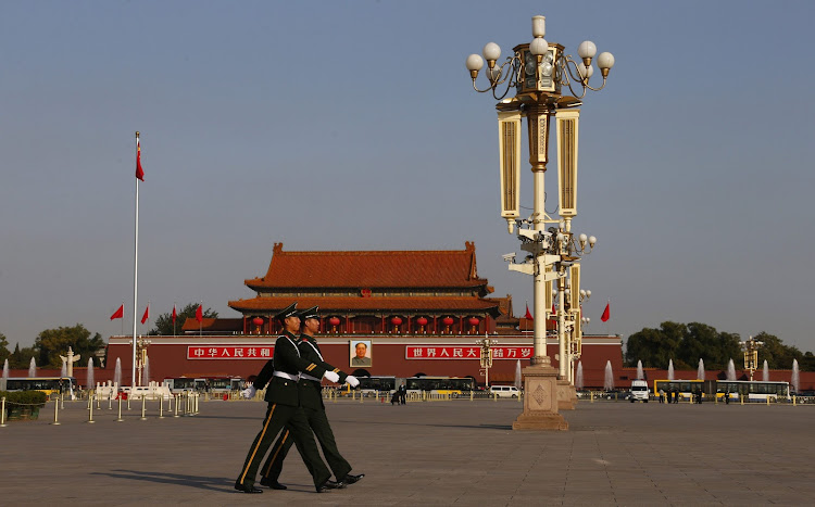 Paramilitary policemen patrol in front of a giant portrait of former Chinese chairman Mao Zedong on Tiananmen Square near the Great Hall of the People in Beijing. Picture: REUTERS