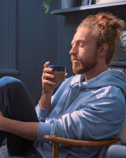 Man winds down in his bedroom with lights dimmed as he sips a cup of evening tea.