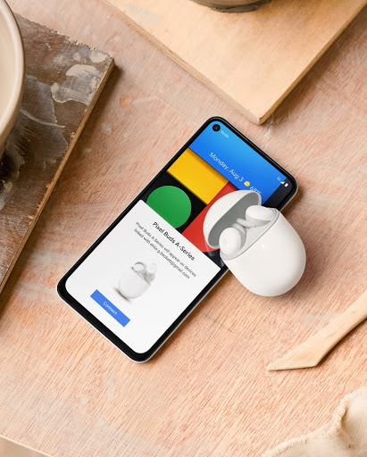 A Pixel phone on a table with Pixel Buds next to it.