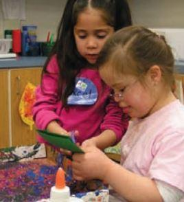 Two girls wearing pink and making crafts at a table. One of the girls is helping the other to cut a green piece of paper.