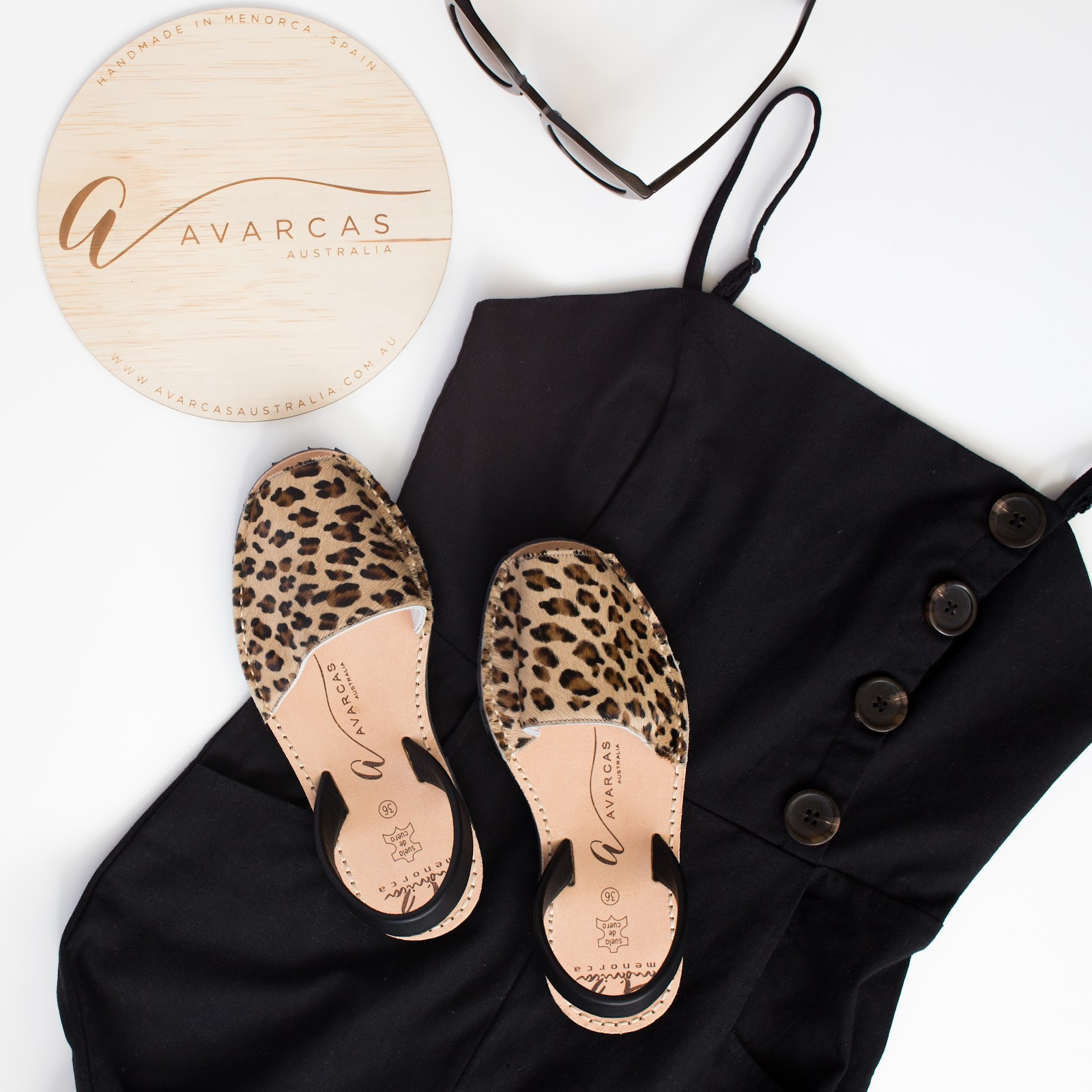Flatlay of black linen dress with leopard print avarcas