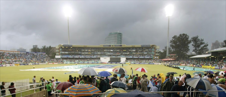 Cricket supporters watch as the covers are put on to the wicket at Kingsmead stadium in Durban. Picture: REUTERS