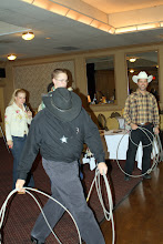 Photo: Tye Halverson, Southwest Air, dips his head to the cow in prepartion of a quick roping.  Crowd laughs.