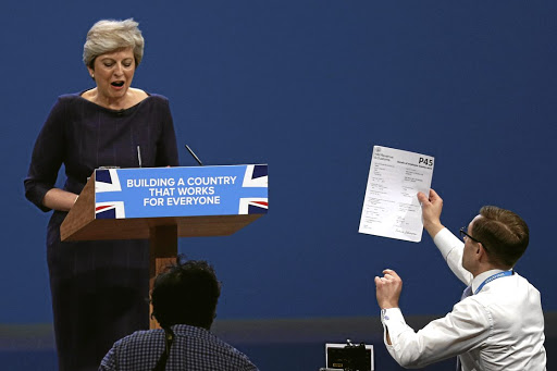 Comic relief: British comedian Simon Brodkin hands a P45 termination of employment tax form to British Prime Minister Theresa May on Wednesday as she addresses the Conservative Party annual conference in Manchester. Picture: REUTERS