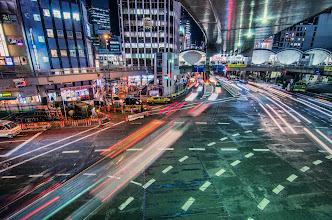 Photo: Cars pass beneath a pedestrian overpass outside Shibuya Station, Tokyo