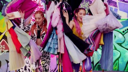 Yuzuna e Suda Anna saindo dentre as roupas para dançar.