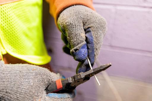 Foto de unas manos con guantes aislantes sujetando una pinza y un cable