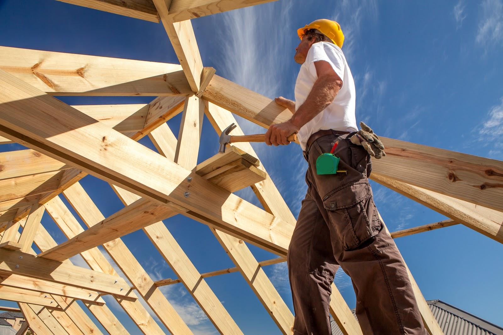 Builder surveying wooden beams