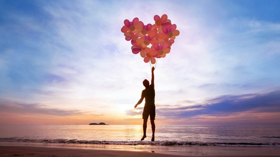 A man floats in the air by the ocean, lifted by many balloons