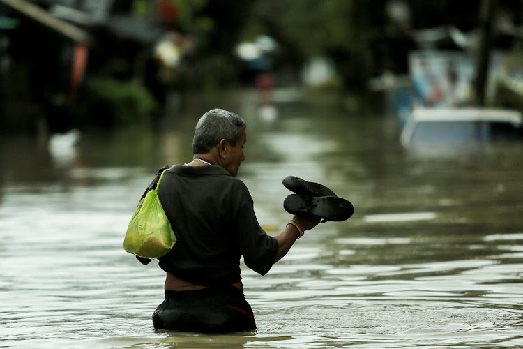 A man walks in a flooded street at Muang district in Nakhon Si Thammarat province, southern Thailand.   Picture: REUTERS
