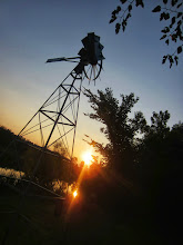 Photo: Silhouette of a windmill against a sunset on a lake at Carriage Hill Metropark in Dayton, Ohio.