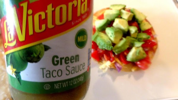 Next, pour about  2 teaspoons of green taco sauce over the avocado.