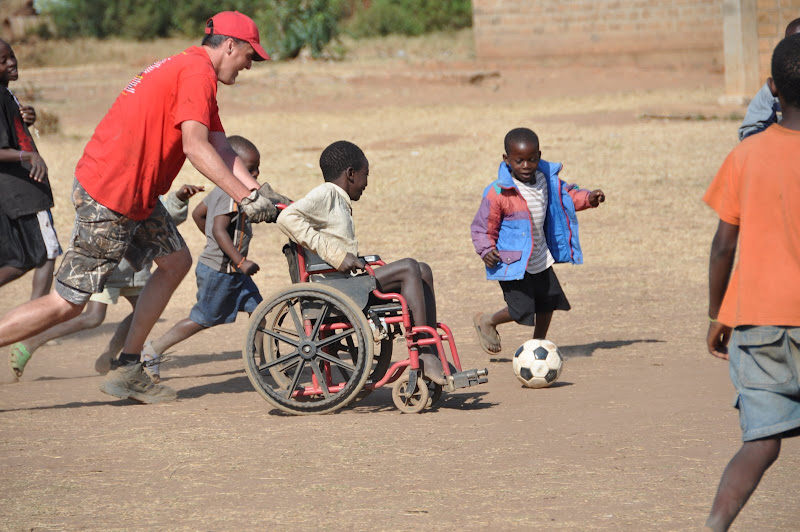 Photo: James Cook is helping a local child in Malawi who is disabled because of polio, playing his first soccer game.