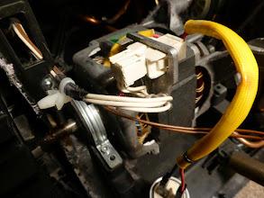 Photo: Die beiden Lager des Motors sind je unter einer Aluminiumschelle, hier links, befestigt, und die mit einer Schraube (vorgesehen waren wohl je zwei, aber bei der Produktion muss es halt schnell gehen … ). Die weißen Stromzuleitungen am Stecker (Bildmitte) ausstecken. Der Startkondensator rechts unten kann dran bleiben, zumal er nur lose eingebaut ist.