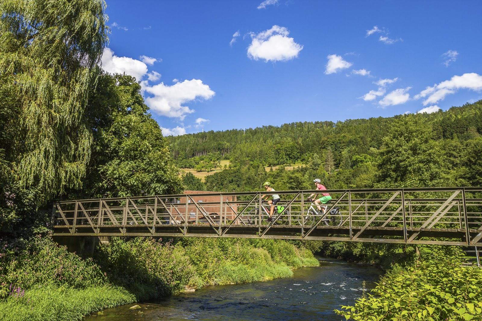 Zwei Radfahrer überqueren auf einer Brücke einen Fluss