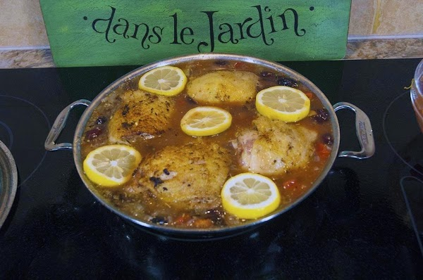 Add the chicken thighs, skin side up, and then distribute the lemon slices over...