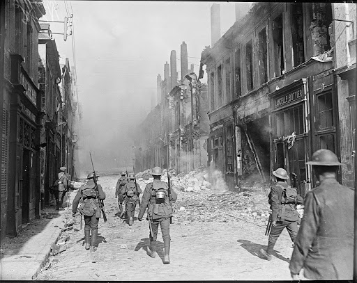 Capture of Cambrai by the British 57th Division. A patrol of the Loyal North Lancashire Regiment in a burning street in the southern suburbs of Cambrai, 9 October 1918.