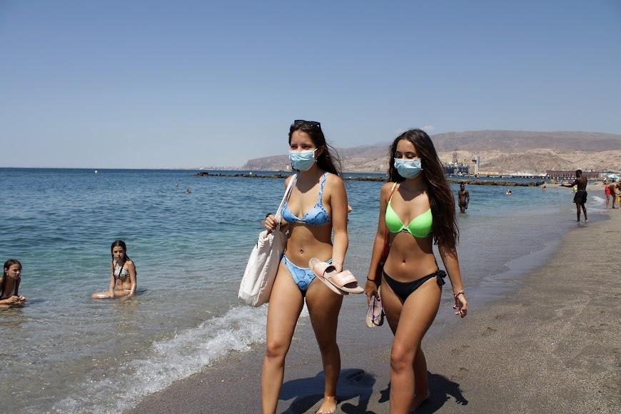Las almerienses Ana y Aroa paseando por la orilla de la playa y con mascarillas.