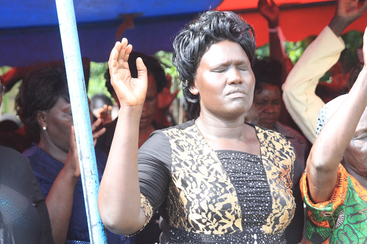 Josephine Kimoi, widow of the elephant attack victim Jackson Chepyegon, 40, joins in prays during her husband's burial at his Sessunin home in Barwessa ward, Baringo North Sub-county on Saturday.