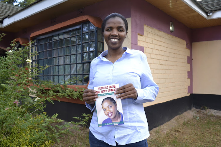 Elizabeth Kogo, 37, holds her book on GBV at her home in Ndaptabwa, Nandi county