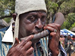 Photo: Das Horn einer Antilope benutzt dieser Teilnehmer als Musikinstrument. Dass der Bläser ein Notabler aus einem Königshaus ist, erkennt man an seinem Gewand in der Königsfarbe Blau-weiß.