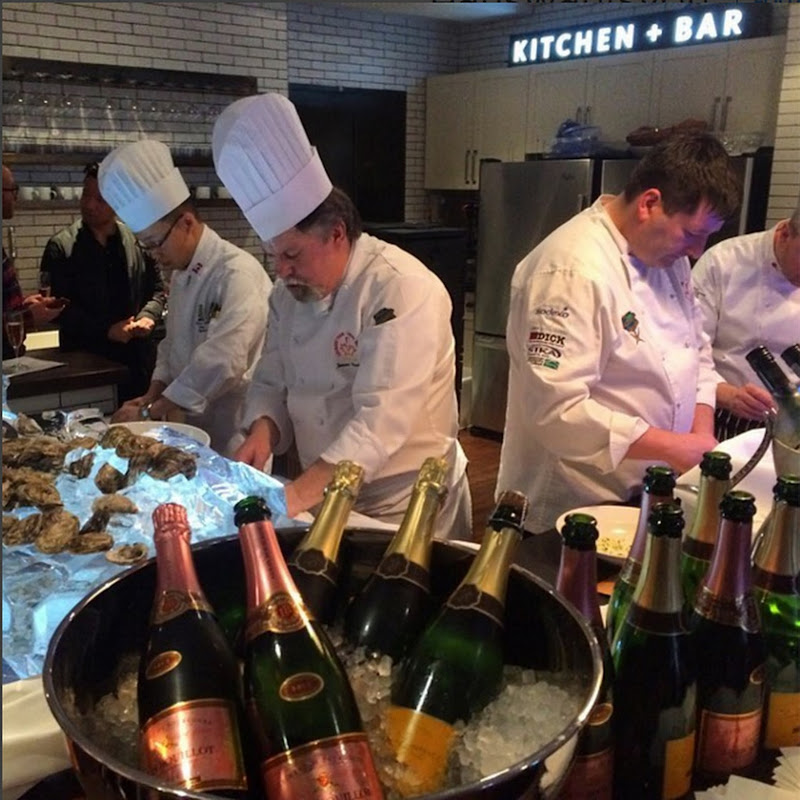 A group of chefs prepping food behind a counter.