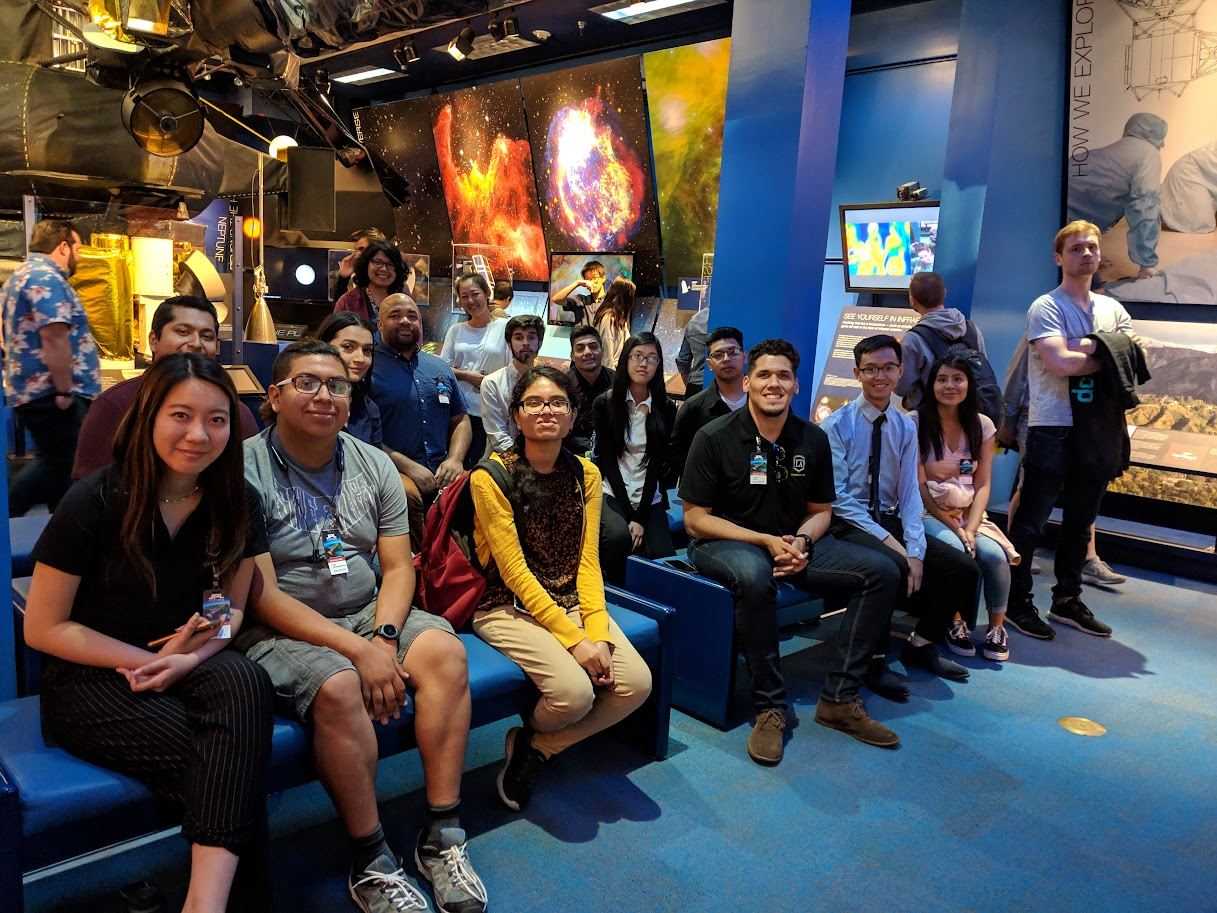 CAPS members in front of an outer space display at JPL