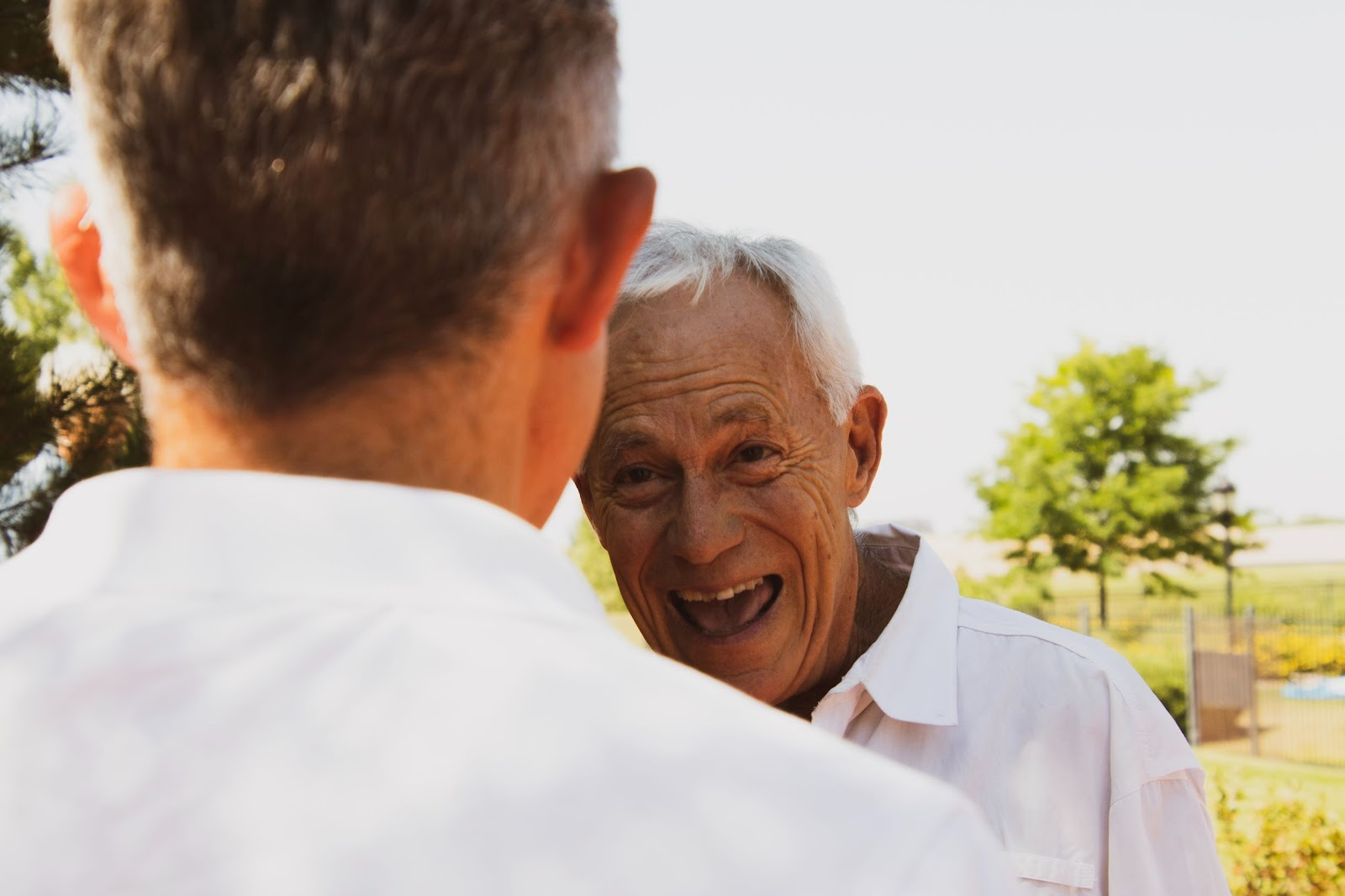 Senior man laughing in conversation with other man