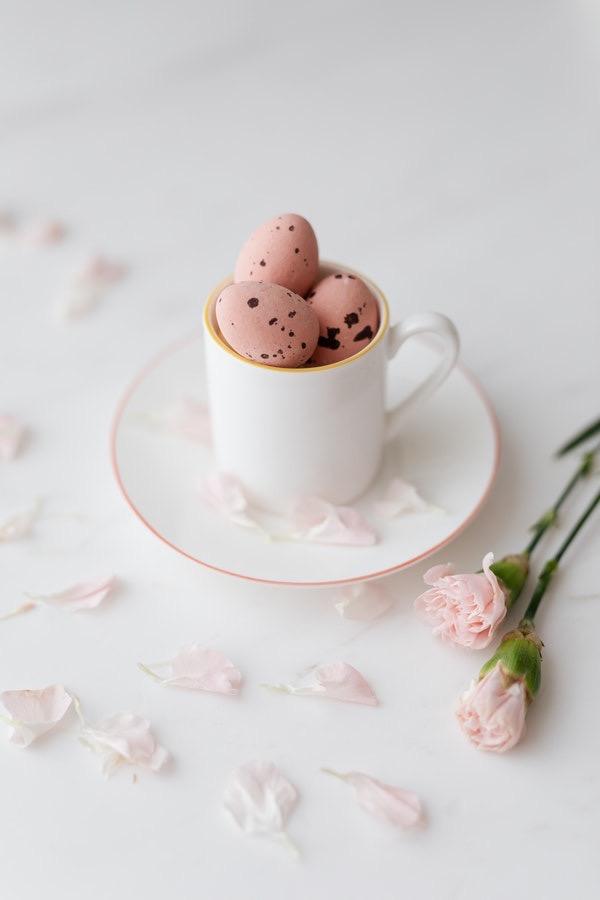 Uma imagem de uma xícara branca com três ovos rosas em um prato branco e uma flor rosa.
