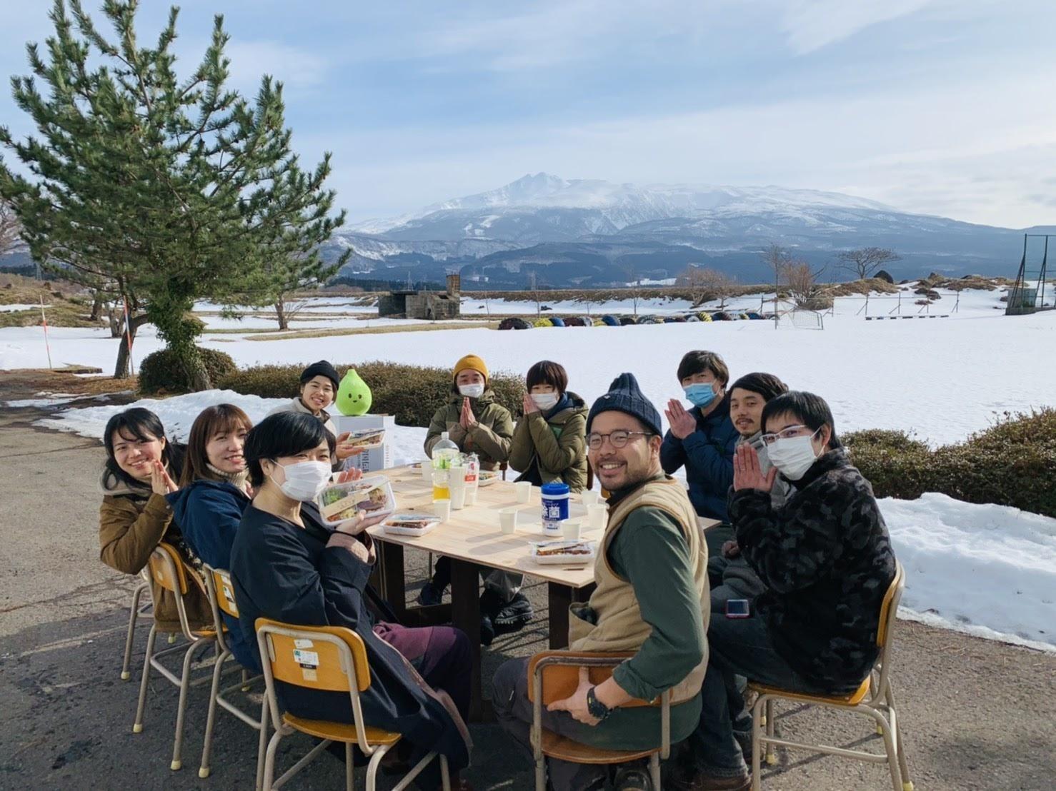屋外のテーブルで食事をしている人たち  低い精度で自動的に生成された説明