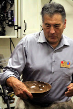 Photo: Clif Poodry is running the Show & Tell session.  Here he gets a good look at a fine walnut bowl by Joe Barnard.