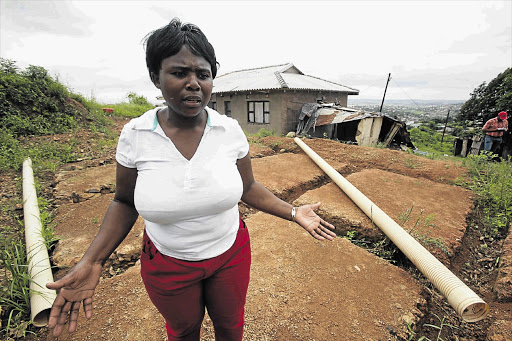 Hlengiwe Msweli next to the site on which the eThekwini municipality wants to build a low-cost house for her in Inanda, outside Durban. Behind her is her home, which she fears will be demolished by the municipality to make way for an access road Picture: THULI DLAMINI