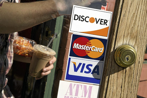 A coffee shop displays signs for Visa, MasterCard and Discover in Washington DC in the US. Picture: REUTERS