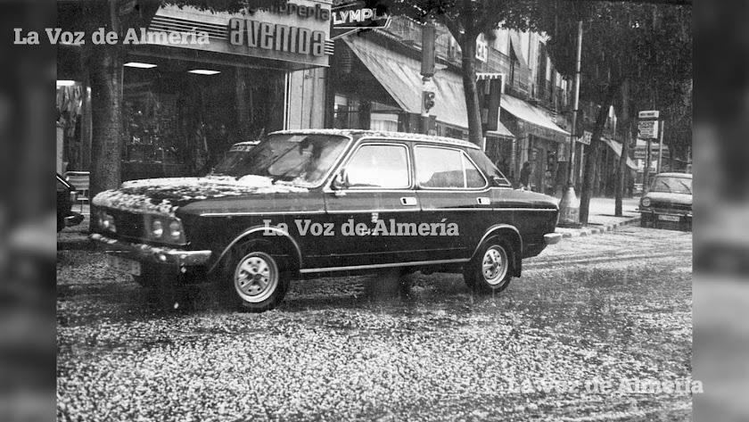 Un taxi pasando por la puerta de la librería Avenida, entre la Puerta de Purchena y el Paseo, en un día de granizada.