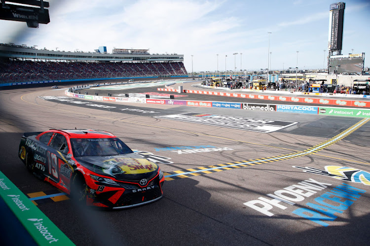 Martin Truex Jnr, driver of the #19 Bass Pro Toyota, crosses the finish line to win the NASCAR Cup Series Instacart 500 at Phoenix Raceway on March 14 2021 in Avondale, Arizona.