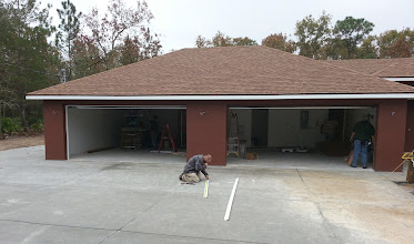 Photo: December 13, 2012 The movers will be unloading into the garage because of the army of contractors working to complete their jobs.  The folks you see here are just finishing up installing the garage doors and the movers are getting ready to unload. Just in time.