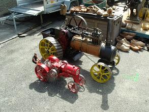 Photo: Deux miniatures de tracteurs; le rouge est équipé d'un moteur thermique, l'autre est à vapeur.