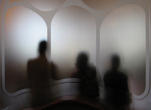 Photo: Ghosts Who said they don't exist? Here is a photo of three of them I took at Casa Battló in Barcelona. Notice how the glass etching goes right through the middle one... :Q