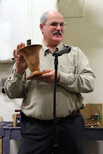 Photo: Secretary Steve Drake discusses his vase on a base.