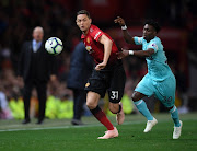 Nemanja Matic of Manchester United battles for possession with Christian Atsu of Newcastle United during the Premier League match between Manchester United and Newcastle United at Old Trafford on October 6, 2018 in Manchester, United Kingdom.