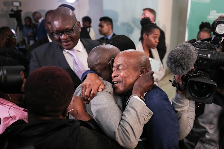 Reverend Joseph Maboe hugs Andrew Peterson in celebration after Former Deputy Chief Justice Dikgang Moseneke ordered that the government pay R1.2-million to the effected families at the Life Esidimeni hearings in Parktown, Johannesburg on March 19, 2018.