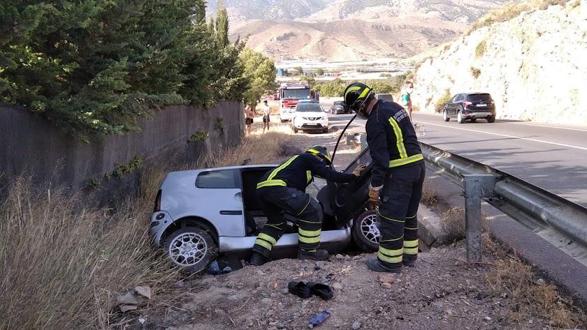 Bomberos del Poniente junto al coche en el lugar del accidente.