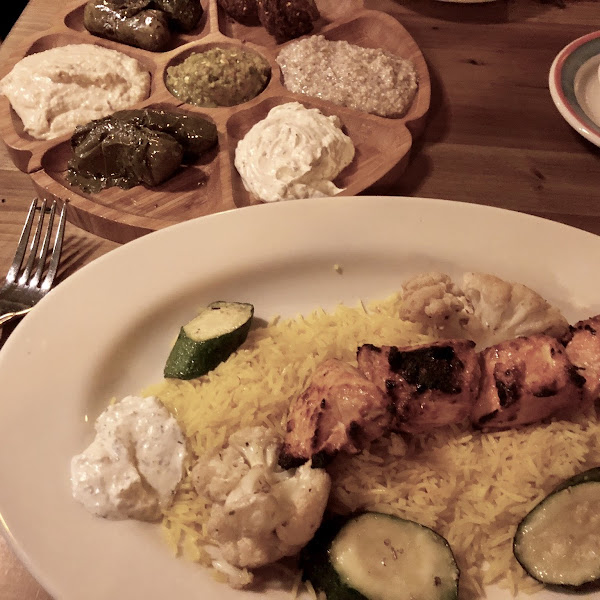 Chicken kebab dinner with vegetarian mezzes in the background
